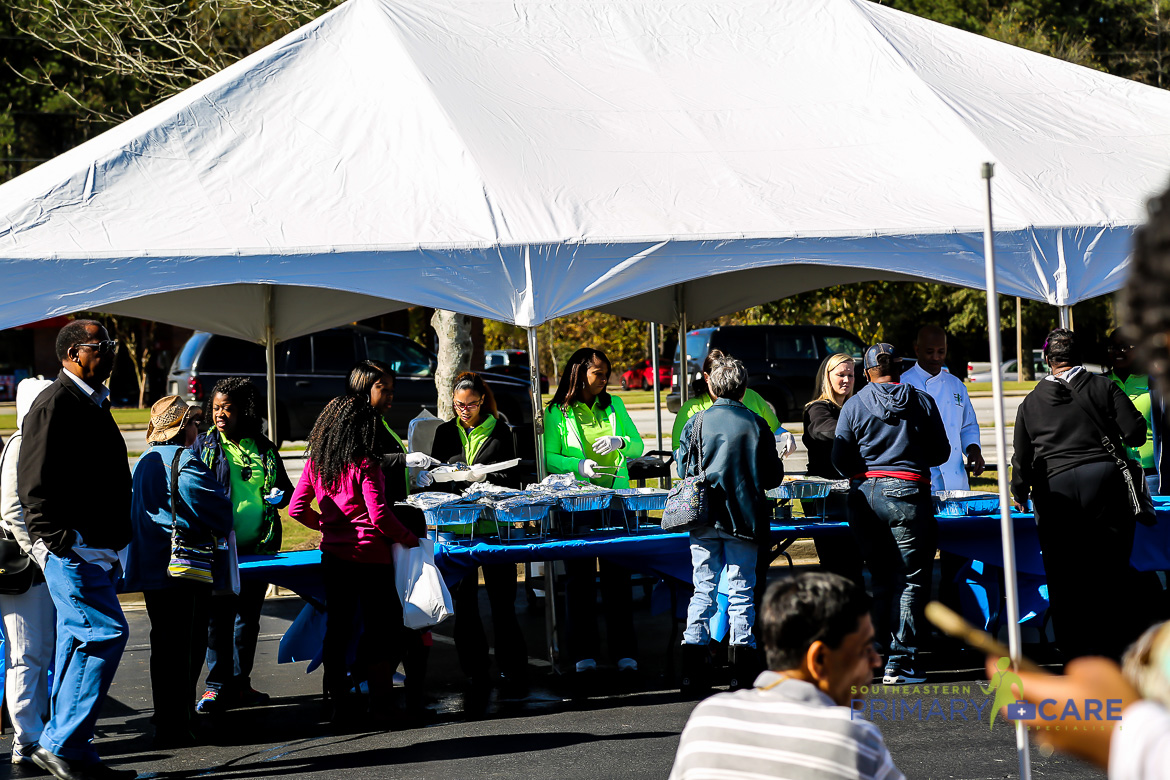 Employees serving food to others outdoors