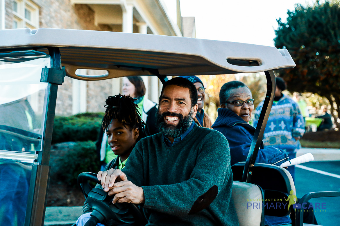 Smilling man driving a golf cart full of people